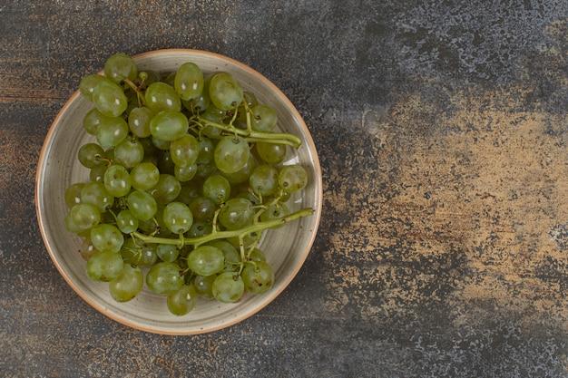 Свежий зеленый виноград на керамической тарелке.