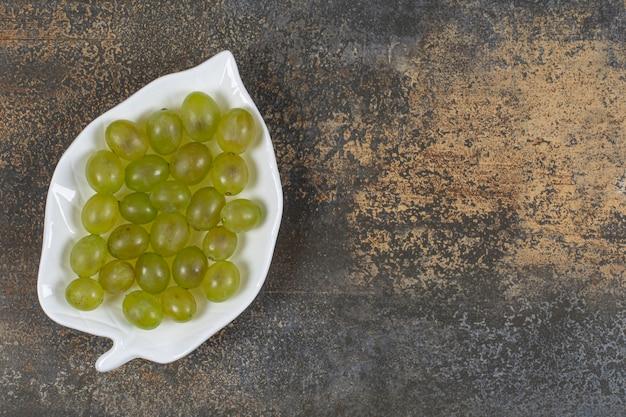 잎 모양의 접시에 신선한 녹색 포도.