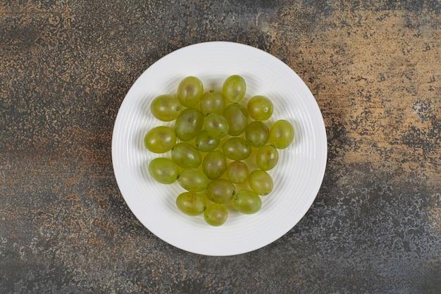 Свежий зеленый виноград на белой тарелке.