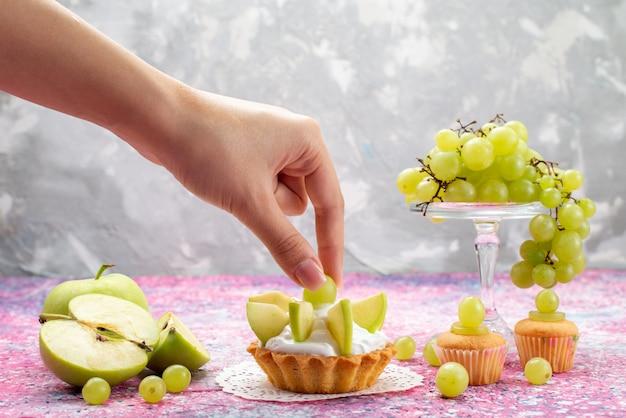 Свежий зеленый виноград цельный кислый и вкусные фрукты с маленькими пирожными, взятыми женщиной на свет