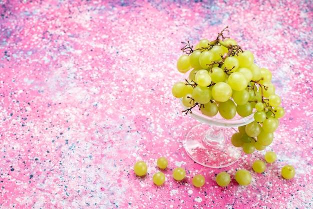 Uva verde fresca intera frutta acida e deliziosa sulla luce
