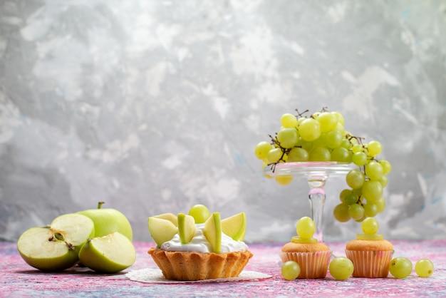 Uva fresca verde intera frutta acida e deliziosa con piccole torte sulla luce