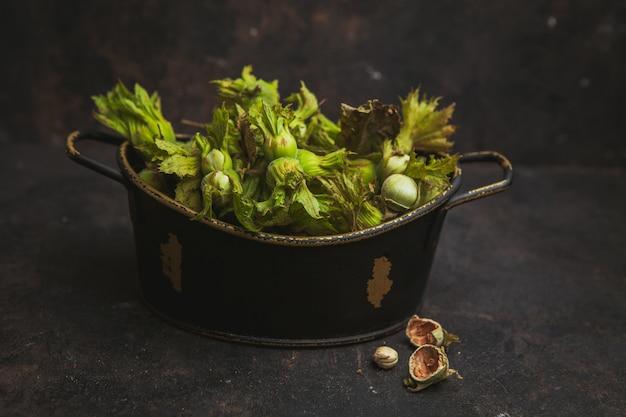 Fresh green hazelnuts in a pot side view on a dark brown