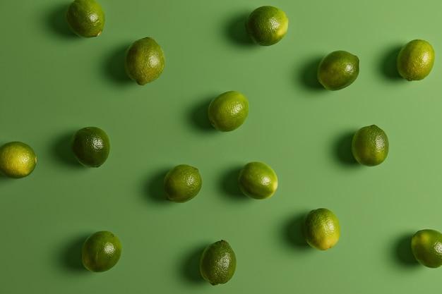 Limette sane verdi fresche sulla superficie luminosa. agrumi utilizzati per accentuare i sapori negli alimenti, guarnire o farcire. consumo di prodotti vegetali ricchi di vitamine e minerali per una buona salute o dieta