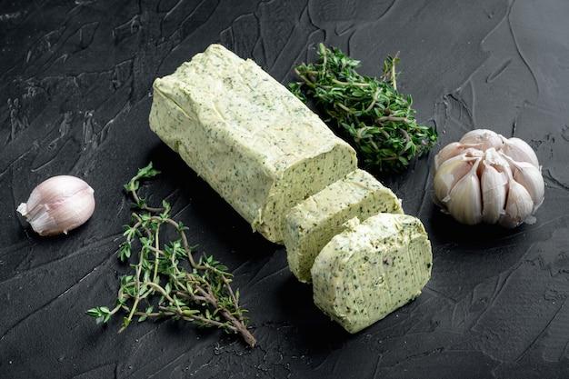 검은 돌 배경에 신선한 녹색 허브 버터 세트