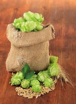 木製の背景に、黄麻布のバッグと大麦の新鮮な緑のホップ