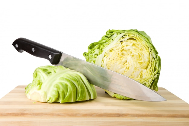 Fresh green iceberg lettuce with knife on wooden chopping board