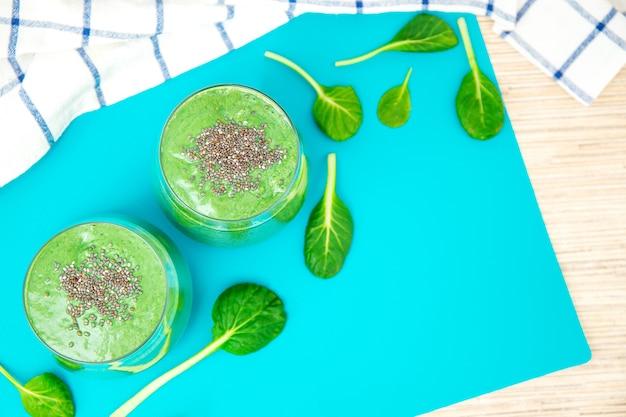 有機緑の果物と野菜で作られた新鮮な青汁スムージー。健康的な食事、ダイエット、菜食主義、デトックスの概念。テキスト用のスペース。フラットレイ。