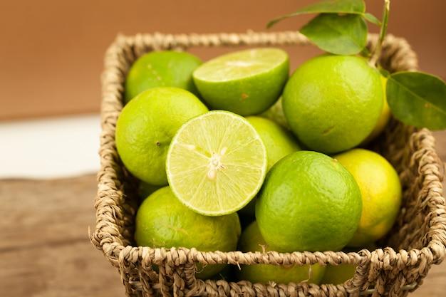 Fresh green lemon in basket on old wooden table
