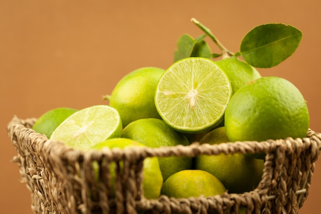 Fresh green lemon with green leaves in basket on brown