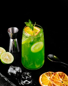 Fresh green lemonade with lemon orange juice and slices and mint.