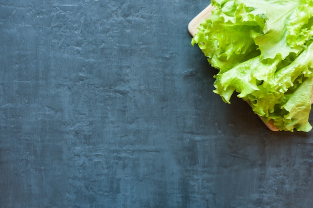 Fresh green lettuce leaf on wooden board, dark background for text.