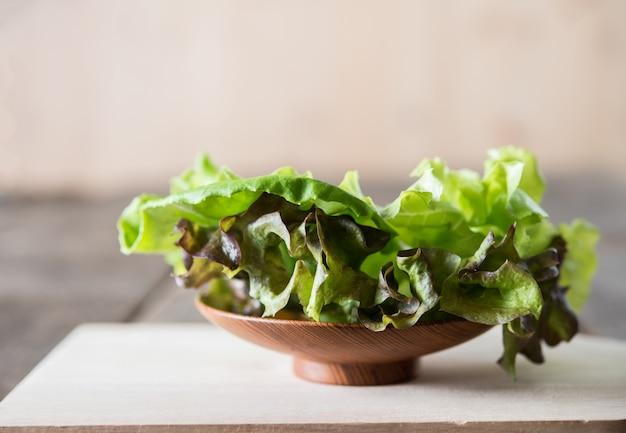 나무 접시에 신선한 녹색 양상추 샐러드입니다.