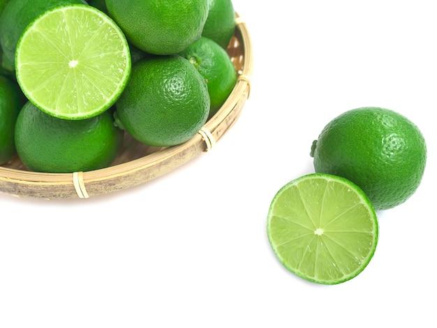 흰색 배경에 고립 된 대나무 바구니에 신선한 녹색 라임.