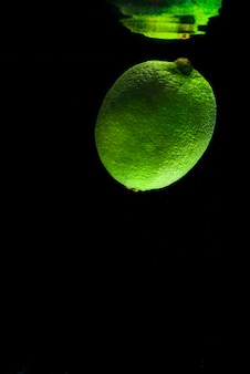 Fresh green lime in water with mirror reflection