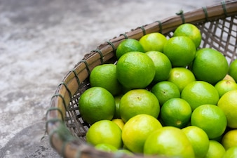 Fresh green limes in wooden basket for sell at the market
