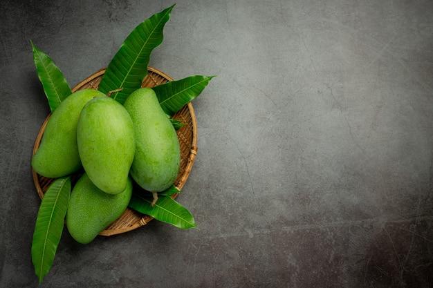 Fresh green mango on dark surface