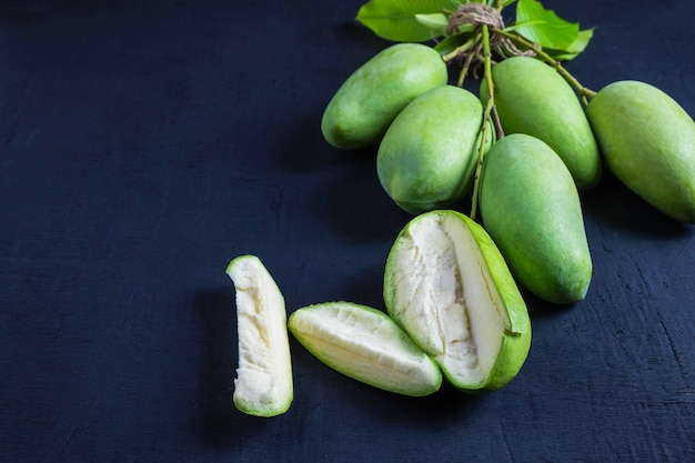 Fresh green mango fruit on a wooden table
