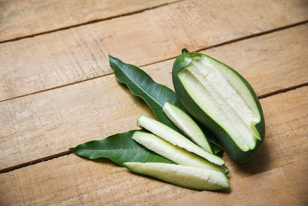 Fresh green mango and green leaves on wooden