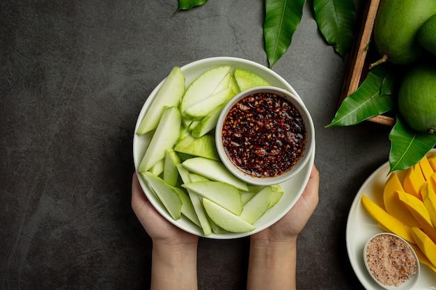 Fresh green mango with sweet fish sauce dipping on dark surface