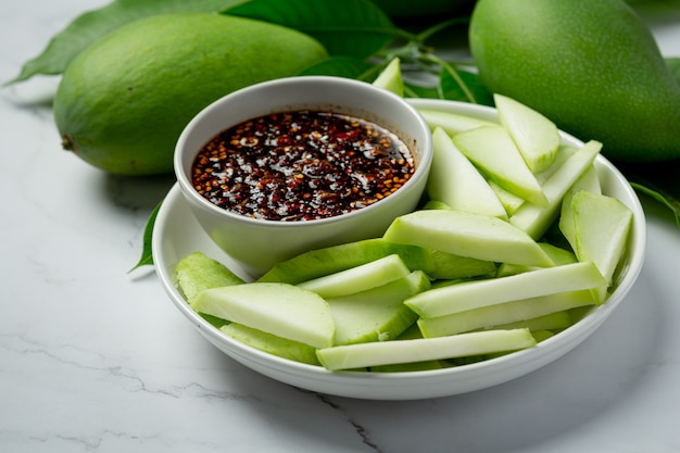 Fresh green mango with sweet fish sauce dipping on white surface