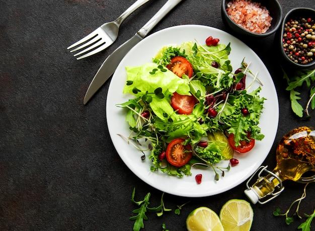 검은 콘크리트 표면에 토마토와 microgreens와 신선한 녹색 혼합 샐러드 그릇
