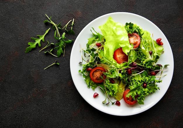 Свежий зеленый смешанный салат с помидорами и микрозеленью на черной бетонной поверхности
