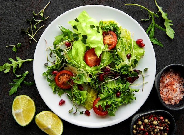 Свежий зеленый смешанный салат с помидорами и микрозеленью на черном бетонном столе. здоровая еда, вид сверху.