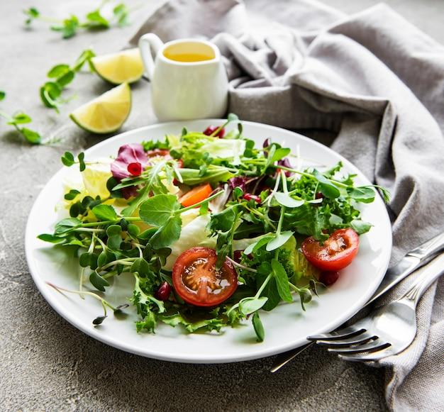 Свежий зеленый смешанный салат с помидорами и микрозеленью на бетонном столе. здоровая еда, вид сверху.