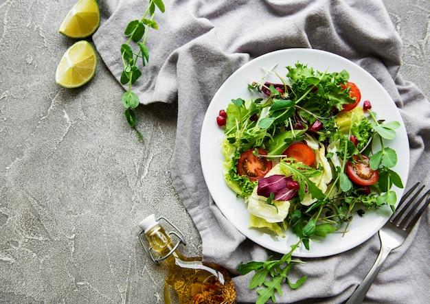 Свежий зеленый смешанный салатник с помидорами и микрозеленью на бетонном столе. здоровая еда, вид сверху.
