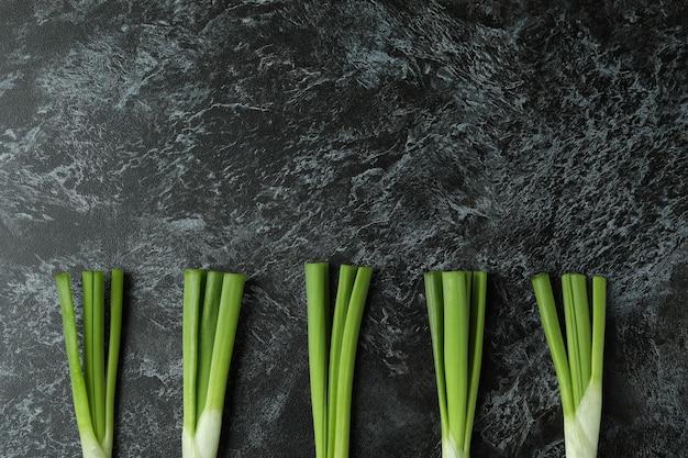 Fresh green onion on black smokey