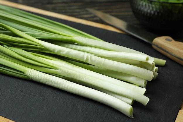 Fresh green onion on cutting board on wooden