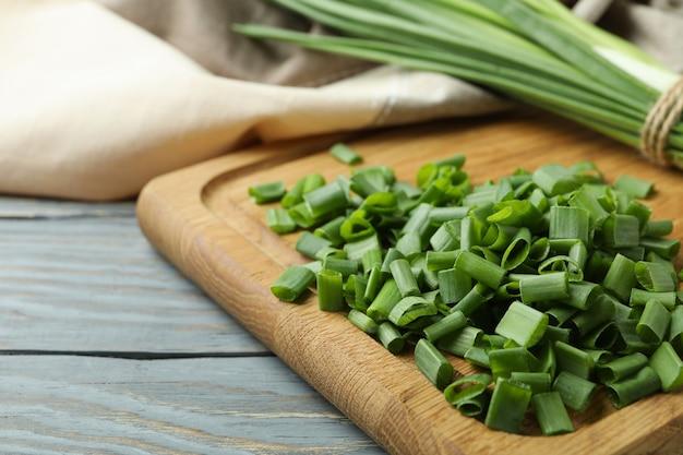 Свежий зеленый лук на разделочной доске, на сером деревянном столе