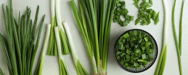 Свежий зеленый лук на белом текстурированном