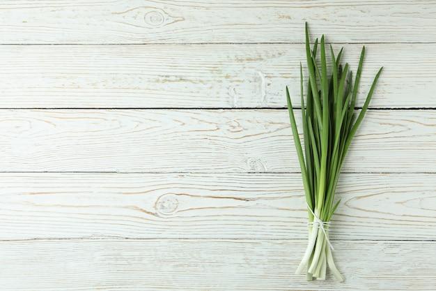 Свежий зеленый лук на белом деревянном