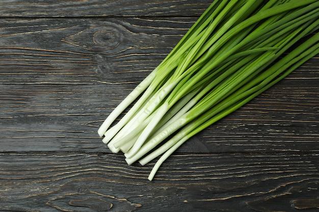 Свежий зеленый лук на деревянном столе