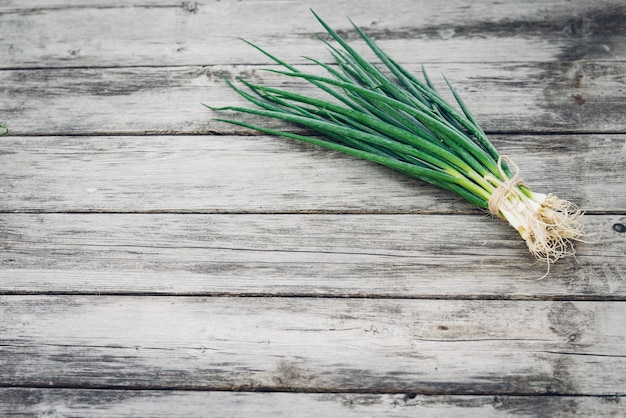 Fresh green onion on a wooden surface. top view. free space