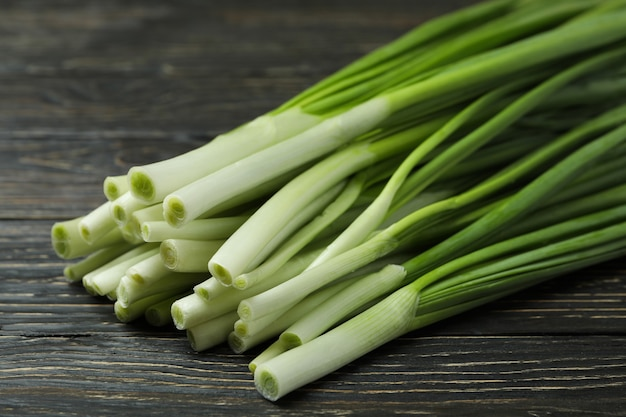 Fresh green onion on wooden table, close up