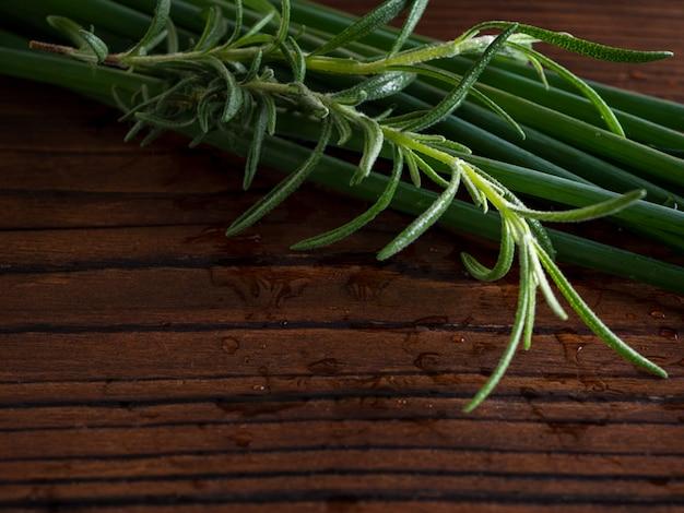 Свежий зеленый лук и свежий розмарин на натуральной деревянной поверхности.