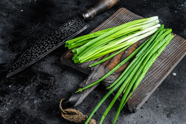 Fresh green onions on a cutting board. black background. top view.