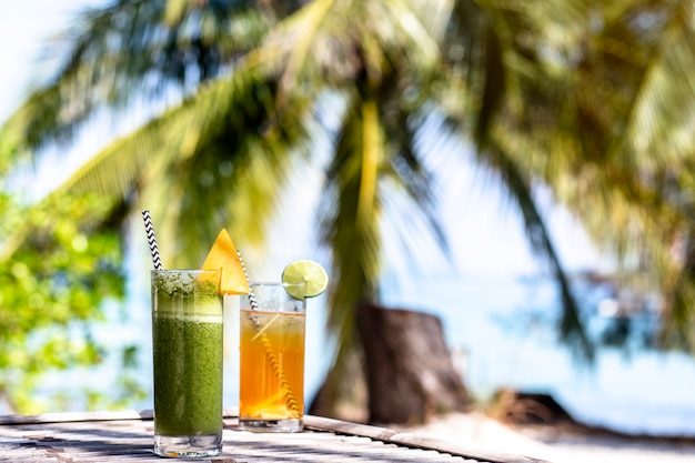Fresh green and orange cocktail on the paradise beach