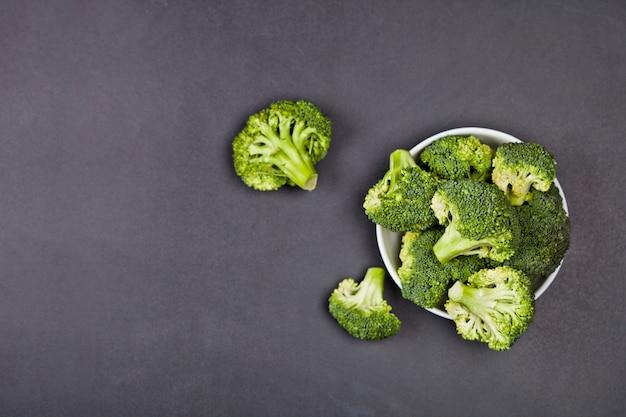 Fresh green organic broccoli in white bowl on black board.