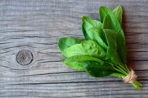 신선한 녹색 유기농 시금치 번들 오래 된 나무 테이블에 나뭇잎. 건강 한 식습관, 해독, 다이어트 음식 성분 개념.