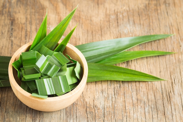 Fresh green pandan in a wooden bowl on wood table,pandan leaves on old wood background