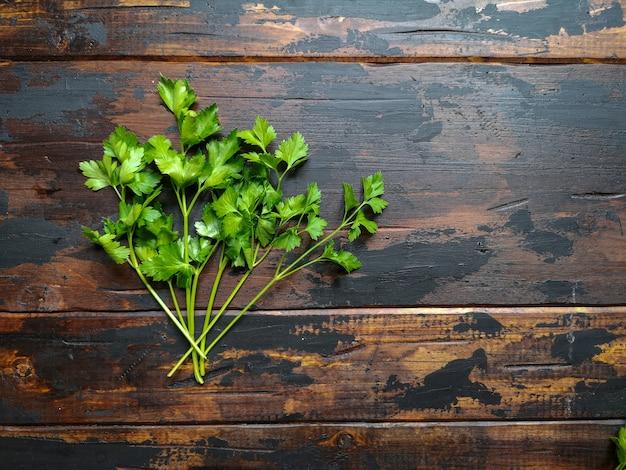 Свежая зеленая петрушка, кинза на деревянном деревенском столе.