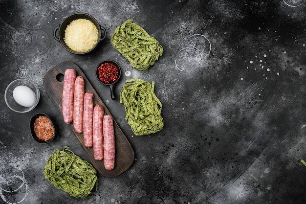 Fresh green pasta and sausages set, on black dark stone table background, top view flat lay, with copy space for text
