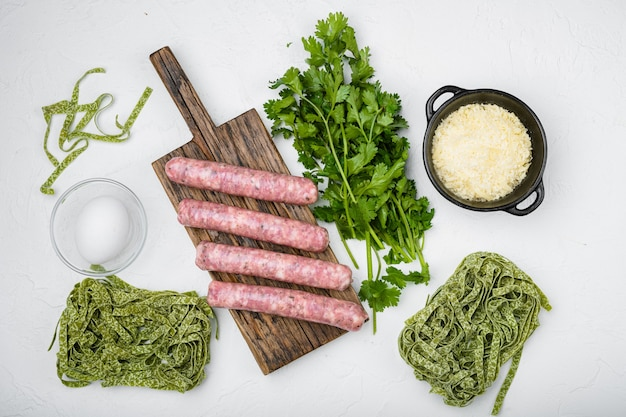 Fresh green pasta and sausages set, on white stone table background, top view flat lay