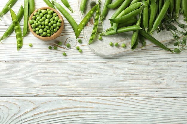 白い木製のテーブルの上の新鮮なグリーンピース