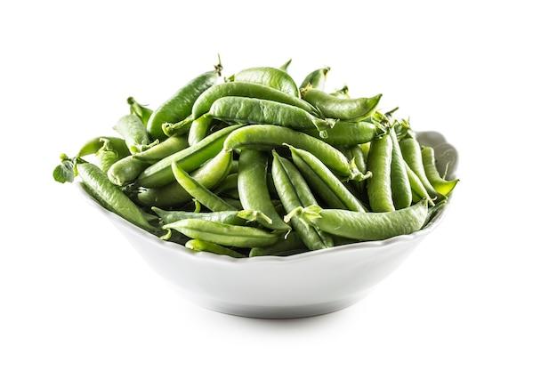흰색 배경에 고립 된 흰색 그릇에 신선한 녹색 완두콩 포드.