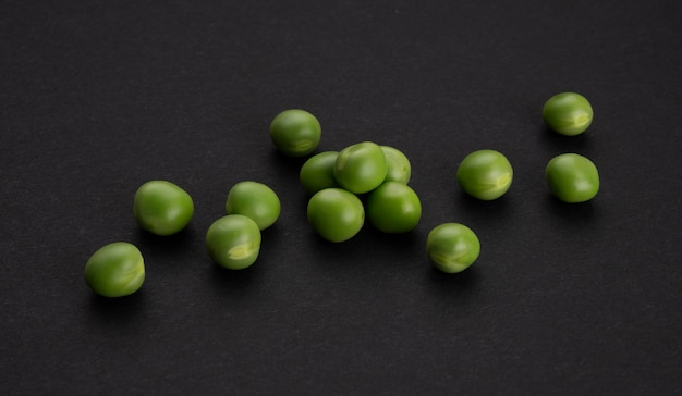Fresh green peas on black background, top view